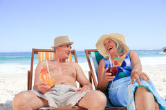 Senior couple sitting on deck chairs. Happy senior couple sitting on deck chairs Royalty Free Stock Photography