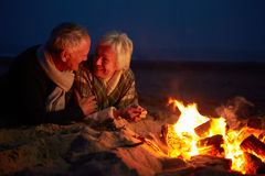 Senior Couple Sitting By Fire On Winter Beach Royalty Free Stock Image