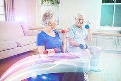 Senior couple sitting on fitness balls with dumbbells. Senior couple lifting dumbbells while sitting on exercise ball at home Royalty Free Stock Photography