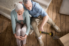 Senior couple sitting on floor at new home. Overhead view of senior couple sitting on floor at new home Stock Image