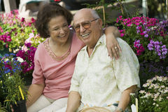 Senior Couple Sitting Among Flowers At Plant Nursery Stock Photos