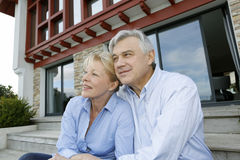 Senior couple sitting in front of beautiful home Royalty Free Stock Photo
