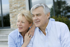 Senior couple sitting in front of house Stock Photo