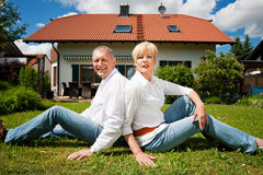 Senior couple sitting in front of their home Royalty Free Stock Image