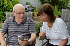 Senior couple reading text messages on mobile phone Stock Images