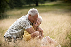 A senior couple sitting on the grass, embracing stock image