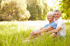 Senior couple sitting on grass together relaxing Royalty Free Stock Image