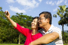 Senior couple sitting on grassland and  taking picture Stock Photo