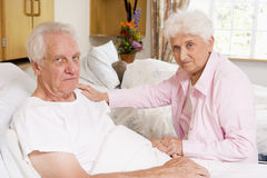 Senior Couple Sitting In Hospital Stock Photo
