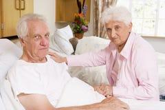Senior Couple Sitting In Hospital Stock Photo