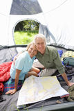 Senior couple sitting inside tent on camping trip, looking at map, smiling, portrait Stock Image