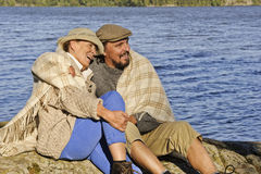 Senior couple sitting by a lakeside with blanket around shoulders. stock image