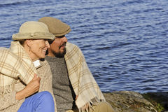 Senior couple sitting by a lakeside with blanket around shoulders. Royalty Free Stock Photos