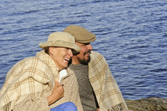 Senior couple sitting by a lakeside with blanket around shoulders. royalty free stock images