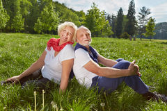 Senior couple sitting on meadow during vacation Royalty Free Stock Image