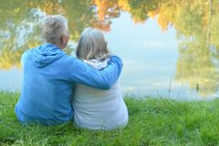 Senior couple sitting near lake Royalty Free Stock Image