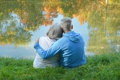 Senior couple sitting near lake Royalty Free Stock Photo