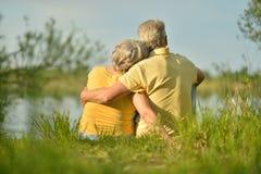 Senior couple sitting near lake Royalty Free Stock Image