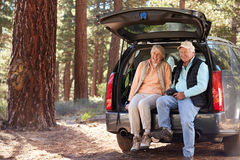 Senior couple sitting in open car trunk preparing for a hike Royalty Free Stock Photos