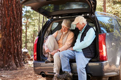 Senior couple sitting in open car trunk preparing for a hike Stock Photos