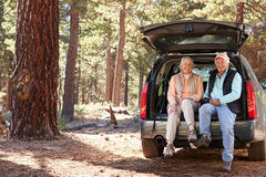 Senior couple sitting in open car trunk preparing for a hike Royalty Free Stock Photo