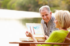 Senior Couple Sitting At Outdoor Table Painting Landscape Stock Photos