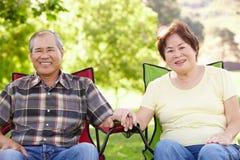 Senior couple sitting outdoors Stock Photos