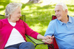 Senior couple sitting outdoors Stock Images