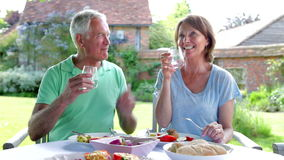 Senior Couple Sitting Outdoors Around Table Eating