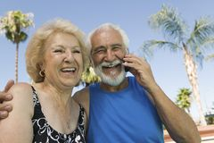 Senior Couple sitting outdoors man using mobile phone portrait. Stock Photo
