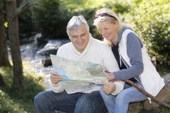 Senior couple sitting outdoors with map Stock Photo