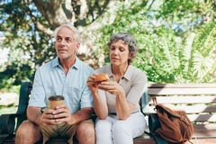 Senior couple sitting outdoors on a park Stock Images