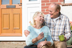 Senior Couple Sitting Outside House With Cup Of Coffee Royalty Free Stock Photography