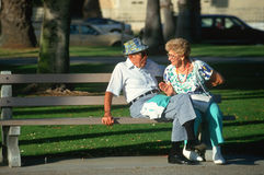 A senior couple sitting on a park bench Stock Photos