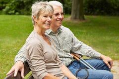 Senior couple sitting on park bench Stock Photo
