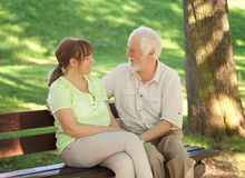 Senior couple sitting on a park bench Stock Photos