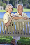 Senior Couple Sitting On Park Bench By Lake. Happy romantic senior couple sitting on a park bench next to a blue lake royalty free stock photography
