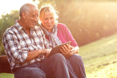 Senior couple sitting on a park bench looking at tablet Royalty Free Stock Images