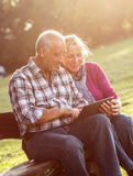 Senior couple sitting on a park bench looking at tablet Royalty Free Stock Image