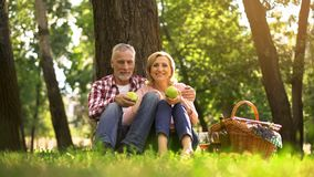 Senior couple sitting in park and eating green apples, picnic, family weekend stock image