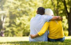 Senior Couple Sitting In Park. Loving senior couple smiling outdoors Royalty Free Stock Photos