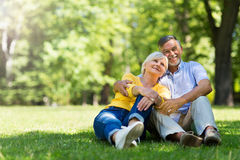 Senior Couple Sitting In Park. Loving senior couple smiling outdoors Stock Photography