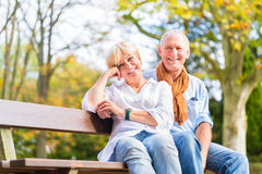 Senior couple sitting on part bench in fall. Senior women and men sitting on part bench in fall Stock Image