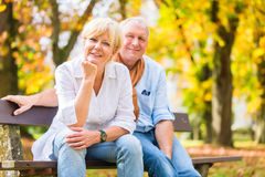 Senior couple sitting on part bench in fall. Senior women and men sitting on part bench in fall Royalty Free Stock Photos