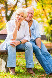 Senior couple sitting on part bench in fall. Senior women and men sitting on part bench in fall Royalty Free Stock Images