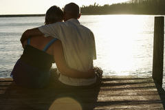 Senior Couple Sitting On Pier By Lake Royalty Free Stock Photo