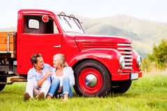 Senior couple sitting at the red vintage car Royalty Free Stock Photo