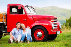 Senior couple sitting at the red vintage car Stock Image