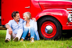 Senior couple sitting at the red vintage car Stock Photography