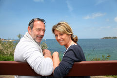 Senior couple sitting by the seaside Royalty Free Stock Photos